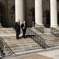 men in suits on steps of a government building